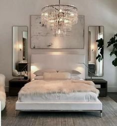 Luxury All White Bedroom Decor Luxury bedroom with white bed, white walls, chrome assents, crystal chandaleer, and sheepskin blanket