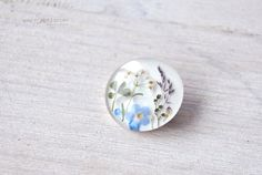 Lucky brooch with 4 leaf clover on meadow. Forgetmenot flowers on white. Summer…