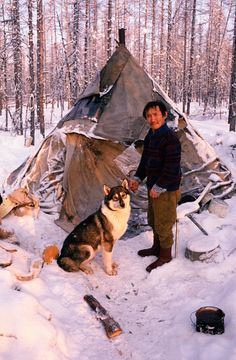 Victor Ivanovich, An Evenk man, with his dog at a reindeer herders' winter camp. Evenkiya, Central Siberia, Russia.