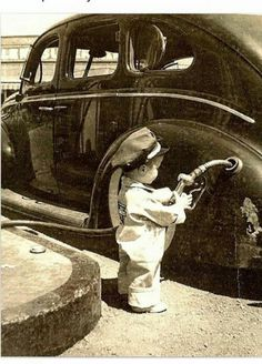 Kid pumping gas in old timey photo