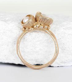 Der Ring ist in Bronze gearbeitet und mit zwei kleinen Blütenkelchen, die mit Süßwasserperlen bestückt sind, gefüllt. Dieser Ring ist frei entwickelt und die Blütenkelche sind durch die Natur inspiriert. Es ist ein handgefertigtes Einzelstück und mit sehr viel Liebe zum Detail erstellt. Die Ringschiene hat eine organische Form und auf dieser sitzen die 2 Blütenkelche. #manufaktur #handwerk #schmuck #einzelstück #unikat #boho #bohoschmuck #blüte #perle #perlenschmuck #bronzeschmuck #natur Bronze Ring, Engagement Rings, Jewelry, Handmade Jewelry, Handcrafted Jewelry, Bronze Jewelry, Organic Shapes, Online Shopping, Boho Jewelry