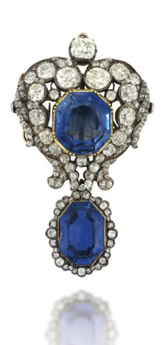 AN EARLY 19TH CENTURY SAPPHIRE AND DIAMOND BROOCH The central octagonal-cut sapphire collet-set to an old-cut diamond heart shaped scrolling border, suspending a detachable similarly-set sapphire and diamond drop, mounted in silver and gold, 6.9cm long, brooch fitting detachable, drop associated