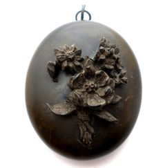 Antique Mourning Jewelry - This is a black Victorian civil war era gutta percha locket pendant. It is hand carved raised flowers and opens to hold photos/pictures. This pendant measures 2 inches by 1.                                                                                                                                                      More