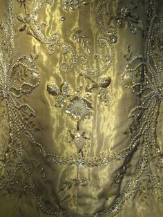 Trond Norén Isaksen: July 2012 Queen Maud's coronation dress, made of gold lamé in the princess style, has scalloped lace sleeves. A decorative pattern of flowers and ribbon bows was embroidered in gilt metal thread, gold-coloured sequins, artificial pearls and diamanté.