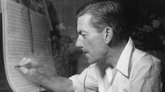 Composer and singer Hoagy Carmichael writing music on the piano in his London hotel room.
