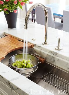 "Guests often help with prep when families entertain, too, so De Giulio puts at least two sinks in a kitchen to allow for multiple cooks. He says that people don't necessarily want to stand around a sink in the island, however, so he ""softens"" its utilitarian look by trimming upper side walls with marble."