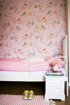 lovely pink birdy wallpaper and a beautiful white iron single bed.