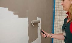 Woman applying the paint colour to the wall