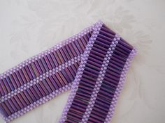 Hand-woven bracelet in shades of purple; for sale now in my shop