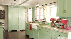 """Folding windows open the kitchen up to the patio in a 1928 cottage designed by Kathryn M. Ireland. Custom tiles from Mission TileWest. Pendant lights from Liz's Antique Hardware. Owner Ursula Brooks says of the green color, """"I didn't want the white house. Everyone was doing white, and it can be incredibly stylish. But this house is funky. It's not perfect, so color seemed the right thing to do."""""""
