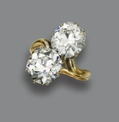 DIAMOND CROSSOVER RING, CIRCA 1910. Set with 2 old European-cut diamonds weighing approximately 3.90 and 4.20 carats, within a simple gold band