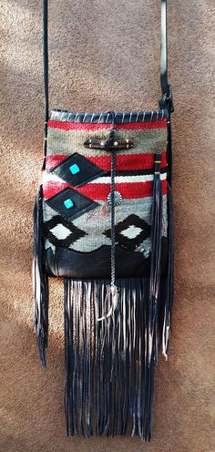 Handbags made from a vintage Navajo textile, vintage horse tack, and deer, elk or cowhide leathers. I embellish the bags with vintage trade beads, turquoise, coral, nickel silver/German silver Concho buttons, nickel silver spots/studs, and deer antler tips.   Ooo So Santa Fe across the body handbag Santa Fe,NM