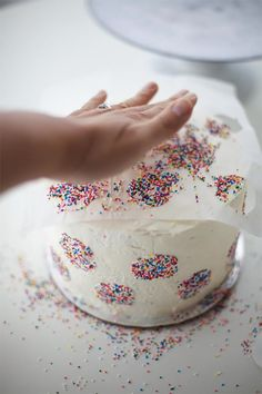 Decorate a cake in just a few minutes by patting sprinkles onto a parchment…