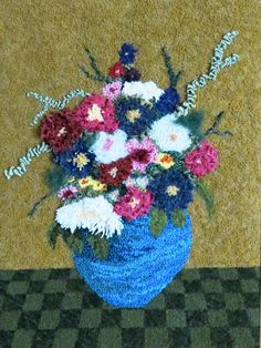 Blue Vase with Flowers . . . hooked in unusual materials the vase is made from plastic grocery bags . . . flowers are assorted materials, background and checkered tablecloth are rug hooking wool