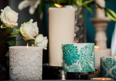 Embossed hand painted pillar candles and white roses create a luxurious wedding table setting.