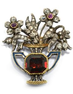 AN ANTIQUE GARNET, DIAMOND AND RUBY BROOCH, 19th century. Yellow gold and silver. Attractive brooch designed as vase of flowers, the vase set with 1 step-cut garnet, in a closed back setting and decorated with blue enamelled handles. The blossoms and leaves set throughout with 67 rose-cut diamonds and 2 small rubies. #antique #brooch