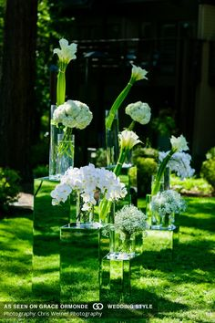 White orchids, hydrangeas, and calla lilies in clear vases on mirror pedestals appear as if they float while on mirror pedestals.
