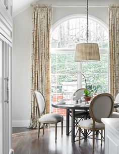 Bringing the curtain pole to the ceiling enhances the height of the delightful breakfast room. - Traditional Home ® / Photo: Emily Followill / Design: Allison Hennessy