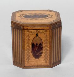 Fine George III satinwood and inlaid octagonal tea caddyLate 18th c.The hinged lid centered by a specimen wood oval panel within a laurel wreath, opening to reveal a covered lined interior, the sides with conforming oval panels and leafy swags, flanked and divided by canted simulated fluted corners. H: 4 3/4, W: 4 3/4, D: 4 1/2 in. Live Auctioneers
