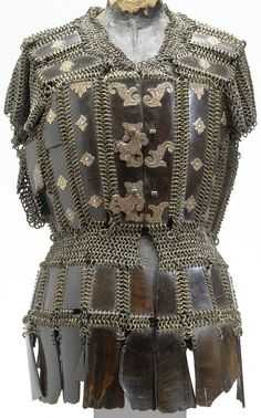 Moro (Philippines) mail and plate armor tunic, 18th to 19th century, the waisted shirt formed of horizontal and vertical rows of rectangular horn plaques attached by butted mail, the chest and shoulder plates embellished with brass rosette sections, two of which act as clasps forming a palmette, approx. 71 cm. long.