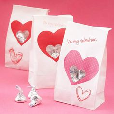 "Valentine's Bag of Kisses - Cut a large heart shape from scrapbook paper and attach it to the bag. Cut out a smaller heart shape in the front and cover the hole with plastic, attaching to the inside of the bag, so the contents won't fall out. Use a red pen to write ""Be My Valentine"" and draw the outline of a heart on the bag to finish the gift."