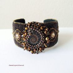 Bracelet | Sanita from Jewelry with Soul.  Ancient ammonite shell cabochon is the focal element, bezeled with chocolate brown, gold and bronze seed beads, freshwater pearls, Swarovski crystals and Czech fire polished beads.