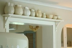 shelf over doorway. yep, i will most likely have so many trinkets, pitchers, bottles, etc that i will need shelves everywhere! if im anything like my mother :)