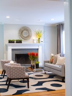 Icy blue living room with pale blue loveseat, two patterned armchairs, a graphic rug and a glass waterfall coffee table
