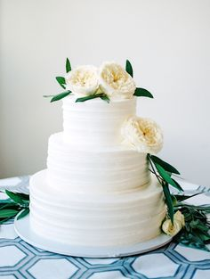 Classic white ranunculus topped wedding cake: http://www.stylemepretty.com/south-carolina-weddings/2016/01/25/organic-industrial-wedding-at-701-whaley/ | Photography: Marcie Meredith - http://marciemeredith.com/