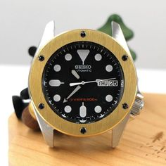The Big Bang Bezel in glittering gold. Designed specifically for SKX013 and 7S26-0030. This bezel is a distinctive and bold statement on a modest sized SKX013.   It has 6 functional screws embedded. These special screws are mirror polished in silver to add a little sparkle. The top of the bezel is brushed while the rim of the bezel is mirror polished.   Available for Pre-Order LuciusAtelier.com (Link in bio)           #seiko #skx013 #skx013mod #seikomod #seikomods #seikomoddiscovery #seikoparts Seiko Skx, Bigbang, Gold Glitter, Discovery, Sparkle, Accessories, Mirror, Link, Silver