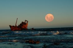 Full moon and one of the beached shipwrecks rusting into the sands of Necochea, on the Argentine coastline
