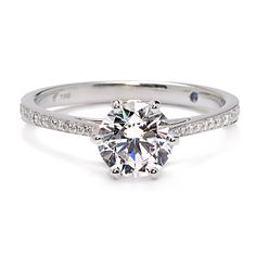 This six prong diamond engagement ring features a round center mounting on a decadently adorned micropave diamond band.