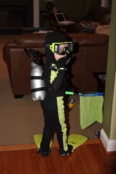 Homemade Finding Nemo Diver costume.  Black long underwear.  Neon green fabric strips are fabric-glued to legs and arms. Diving cap is sewn from a ski-cap pattern.  Tank is a painted soda bottle.  At the hardware store I found the silver crank, and black tubing which I glued to the top of the tank.  Black nylon strapping was sewn together to hold the tank and hang on the shoulders.  The net is strung around a wire hangar, with the end cut short and stuck into a plastic golf club handle.