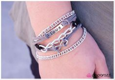"""I Will Never Break Your Heart ~ Gray and black strips of suede are tied to silver details bordered by links of silver chain. Silver details include a rectangular plate etched with the word, """"Love"""" and an infinity symbol. Features an adjustable clasp closure."""