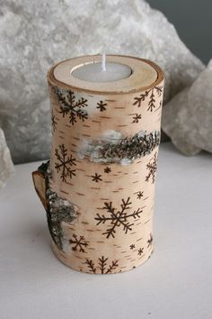 Snowflakes carved into side of hollowed out Birch tree log to be used for holding a candle. A Dremel tool would make an easy task of this project. #WoodlandChristmas