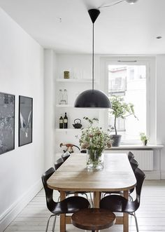 dining room with white walls, light wood table, black chairs, industrial black pendant, plants