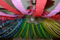 Hang a hula hoop from the fan blades then attach one end of the streamers to the hoop and then adhere the other end to the walls.