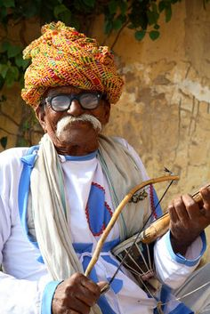 Portrait of Rajasthani man with turban playing traditional Indian stringed instrument, Sarangi.