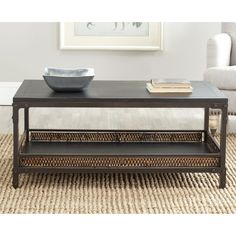 This modern wood coffee table has wicker accents to give it an exotic feel. The under-table shelf gives you additional storage for books and other items. Made of wood, wicker, and iron, this table blends well with nearly any type of decor.