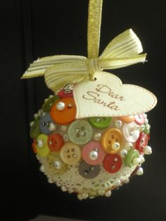 Stryrofoam ball ornament made using buttons and sewing pins.