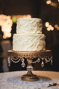 This simple two-tiered buttercream-frosted #weddingcake gets a boost of #glam with that gold jeweled cake display! {@tonygambino}