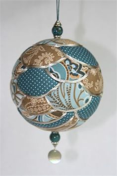 "Kimekomi Ornaments : Kimekomi means ""to tuck"" in Japanese.  Kimekomi ornaments are made by tucking small pieces of fabric into a foam ball.  The seams are then covered with satin cord."