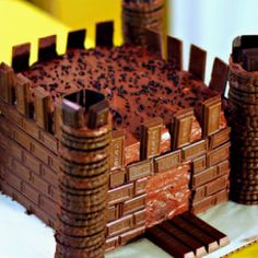 Chocolate Castle Cake: - base square chocolate cake covered with chocolate icing - pillars are chocolate cookies - bricks made of mini hershey bars - moat made of kit-kat bars