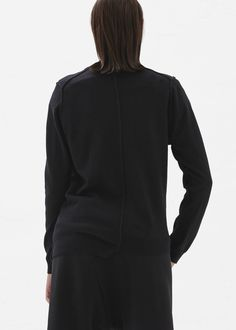 Asymmetrical pullover sweater in a black cotton and wool blend with inside-out seam detail throughout, slit at bottom hem, and ribbed neck, cuffs, and bottom hem. Hand wash in cold water. Dry flat on towel.