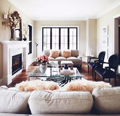 white fireplace + black upholstered chairs + glass-top coffee table + fur pillows + hardwood flooring