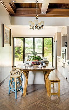 The kitchen counter gets an extension by means of a wooden table, which is made from different types of wood. The old stools on the other hand get an update through bright aqua paint.