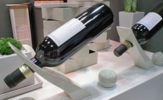 O suporte para garrafa de vinho com design de Yamakyu Urushi, na linha Kasane, é feito de madeira e laca, equilibra a garrafa (cheia)  perfeitamente na mesa.