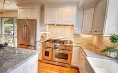 Gray granite compliments a white subway tile backsplash and clean, white cabinetry.