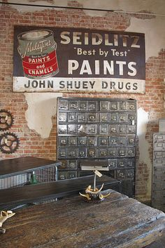 Rustic work area with a great old metal sign. Love the file drawer cabinet!