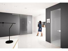 Porta a battente, serratura magnetica, stipite Plain filo muro in alluminio. Porta scorrevole esterno muro Absolute, doppio maniglione HG400 cromo satinato, scorrimento a vista in alluminio. Vetri grafite, decori sabbiati Graphic.